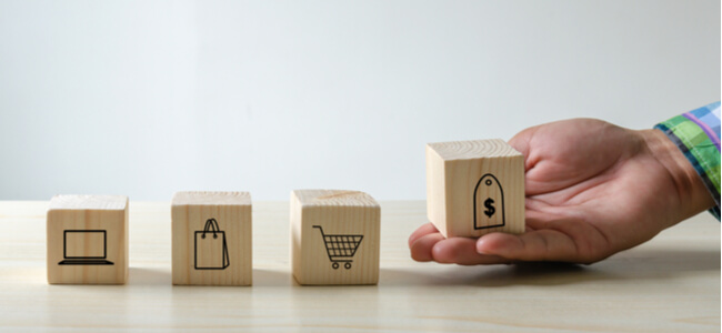 Hand holding cubes shopping icons